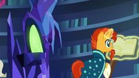 Sunburst looking through a book in the library S7E26