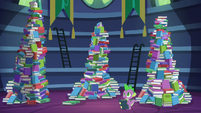 Spike standing besides the mountains of books S5E22