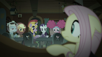 Fluttershy looks at her friends from behind couch S5E21