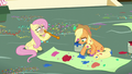 Applejack paints a banner and Fluttershy blows a balloon S5E11.png