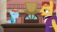 Rainbow grins smugly at hotel clerk S6E13