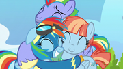 Rainbow Dash happily hugging her parents S7E7