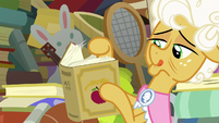 Goldie Delicious looks through history book S7E13