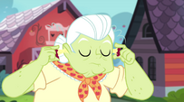Granny Smith using two apple cores as earplugs EG2