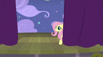Fluttershy behind the opening curtains S8E7