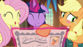 Applejack blushing and turning the certificate over S5E19.png