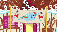 Rainbow Dash in front of birthday banner S4E12