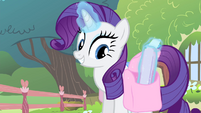 Rarity levitating a flyer from her saddlebag S4E14