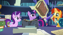 Sunburst levitating a large encyclopedia S7E25