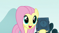 Fluttershy holding the EEA guidebook S8E2