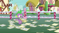 Spike surrounded by scattered contest flyers S7E9