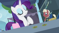 Rarity pointing at one of the brooches S4E22