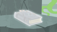 Star Swirl's journal glowing in a white aura S7E25