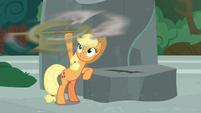 Applejack spins Rockhoof's shovel in her hoof S7E25