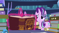 Twilight looking through a book about portals S7E26