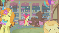 Apple Bloom stands next to the chocolate pony S1E12