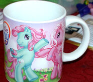Pinkie Pie with Minty on one side of a mug