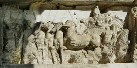 Bas-relief of Roman driver in four-horse chariot, facing left.