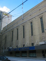 """An exterior view of a building. The building has a sign that says """"Maple Leaf Gardens"""" on the front."""