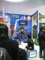 Inside a large, brightly lit convention center room with white walls is positioned a promotional display booth for a video game. A saleswoman clad in a blue shirt and skirt and a red bowtie motions towards several illustrations on the booth, explaining their implications. The illustrations are anime-styled and depict several outlandish and brightly colored creatures. Three men in dark jackets, one at a , watch the demonstration.