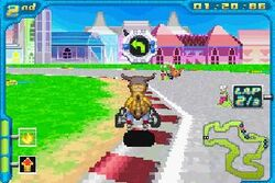 An orange bipedal dinosaur rides a small go-kart around the corner of a paved race track. Two other racers are visible around him. Futuristic buildings appear in the daytime background. Stylized features such as time remaining and a small map of the course adorn the edges of the screen.