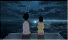 Onodera y Ichijo platicando en un muelle de la playa