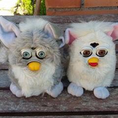 A gray Foobie next to a white Furby