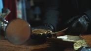 2x01 médaillon du Spectre loupe mains M. Gold gants boutique d'antiquités