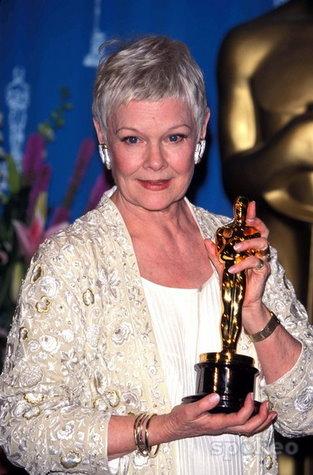 Judi Dench holding an Oscar.