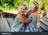 Stock-photo-two-little-girls-in-the-same-jeans-dresses-dabble-hugging-and-have-a-good-time-on-a-summer-sunny-day-619130408