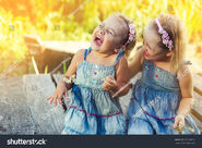 Stock-photo-two-little-girls-in-the-same-jeans-dresses-dabble-hugging-and-have-a-good-time-on-a-summer-sunny-day-619130615