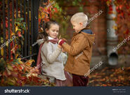 Stock-photo-the-boy-is-holding-the-hands-of-the-grapes-and-the-girl-is-sitting-in-the-autumn-park-walking-in-704114590