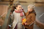 Stock-photo-a-romantic-walk-of-the-boy-and-a-pretty-girl-holding-an-autumn-maple-bouquet-walking-in-the-city-705772000