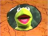 Snapshot of Kermit in a circle of a orange background for the end credits of Muppet Treasure Island Sing-Alongs