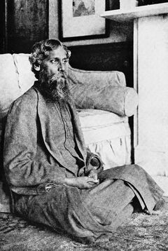 Black-and-white photograph of a bearded middle-aged man dressed in dark robes. He is seated on the floor of an elegantly appointed room and is in front of a plush sofa; he gazes fixedly away to the right, away from the camera.