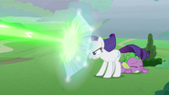 Rarity protects Spike with magic shield S9E25
