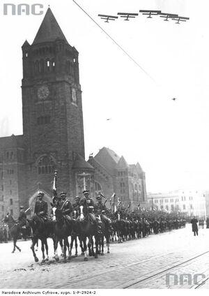 Oddziały 15 Pułku Ułanów Poznańskich defilują ulicą Święty Marcin. U góry widoczne samoloty wywiadowcze 3 Pułku Lotniczego.