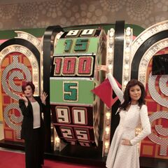 Julie Chen poses as a Barker's Beauty while her <i>Talk</i> co-host Sharon Osbourne hopes to land on the dollar as she tries her luck at the Big Wheel