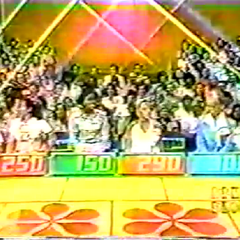 Contestant's Row from 1975: Shortly before the show debuted to one hour, the seat covers were changed to blue and have been updated to reflect the show's current name. Notice the second podium is green and the fourth podium is blue.