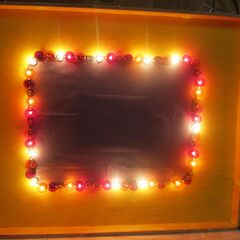 Homemade light border, made of plywood, yellow paint, black construction paper, red and orange G40 bulbs and clear S6S bulbs to create the same pattern as on the show.