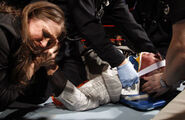 Stephanie McMahon cries as EMTs tend to her injured father Vince RAW 1.19.09