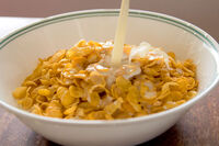 Cornflakes with milk pouring in