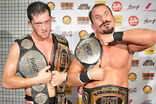 Bobby Fish and Kyle O'Reilly, two black-haired Caucasian men in black reDRagon T-shirts with the ROH World Tag Team Championship belts