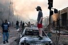 A man stands on a burned out car on Thursday morning as fires burn behind him in the Lake St area of Minneapolis, Minnesota (49945886467)