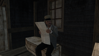 Eldin Grubb reading a newspaper while sitting on a coffin