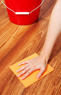 Woman s hand cleaning the floor with yellow sponge