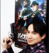 Yasuhiro Ampo poses with Biohazard 5 Poster
