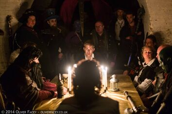 Explorers gathered around a candlelit table.