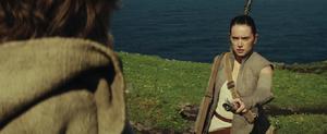 Rey hands Luke Skywalker his old lightsaber