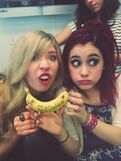 "Ariana & Jennette making grimaces, holding a banana that says ""We love DanWarp"""